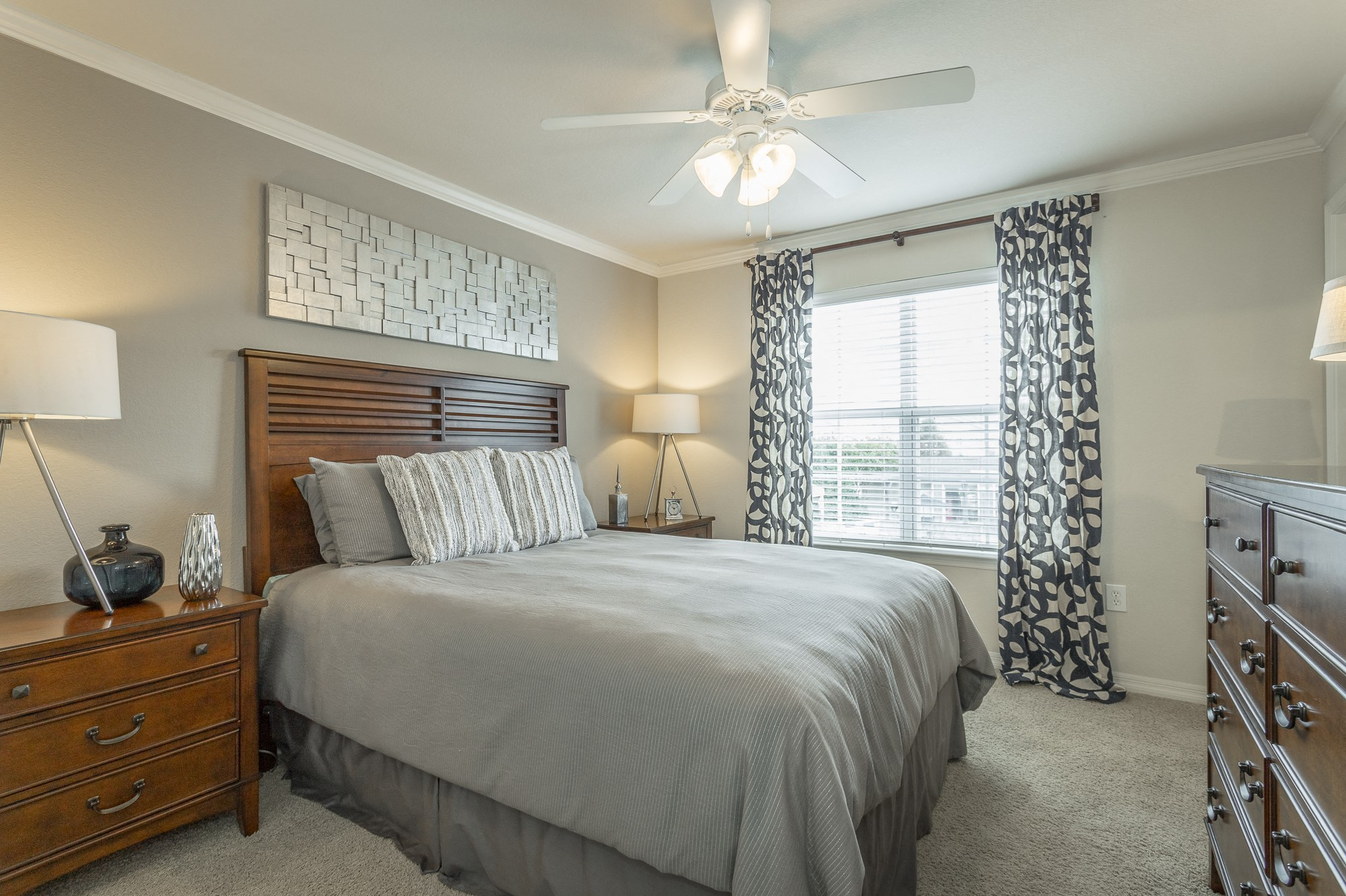 Beautiful bedroom at Amberleigh Ridge with plush carpeting, overhead lighting, designer ceiling fan and large windows