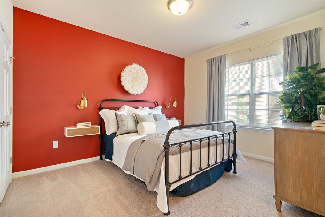 Spacious bedroom with plush carpeting and large windows at Hawthorne at Horse Pen Creek