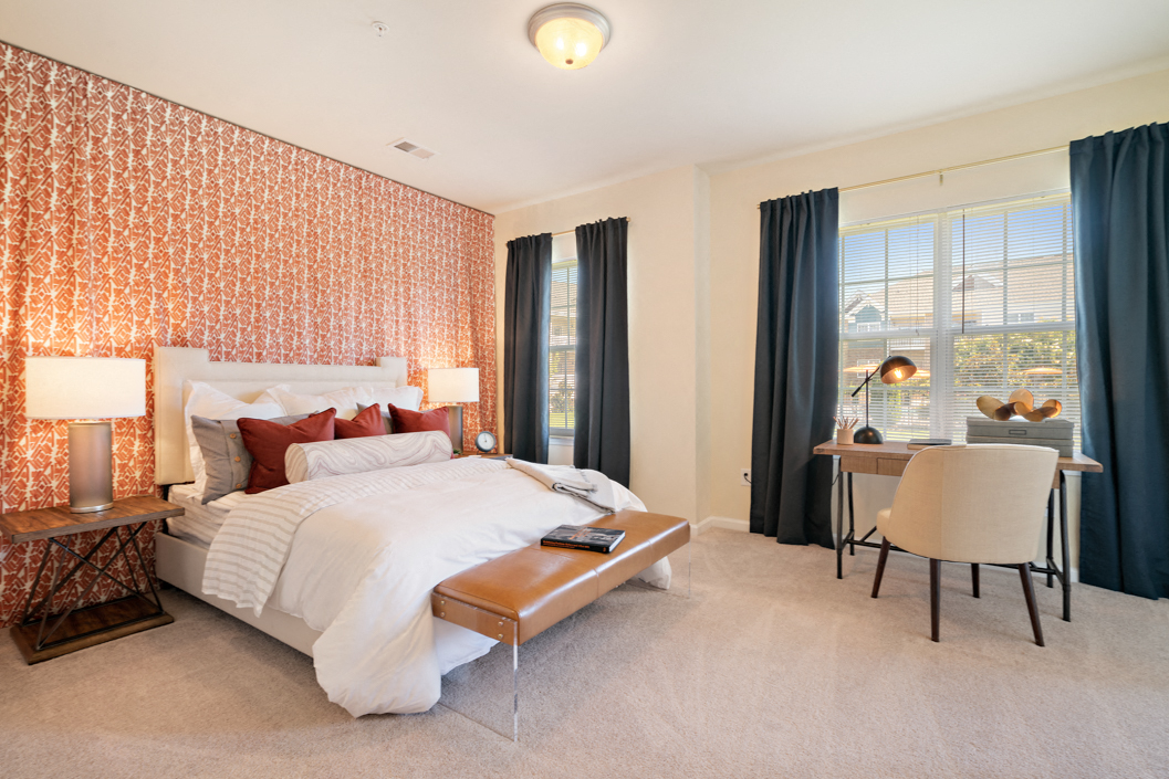 Master bedroom with plush carpeting and large windows at Hawthorne at Horse Pen Creek
