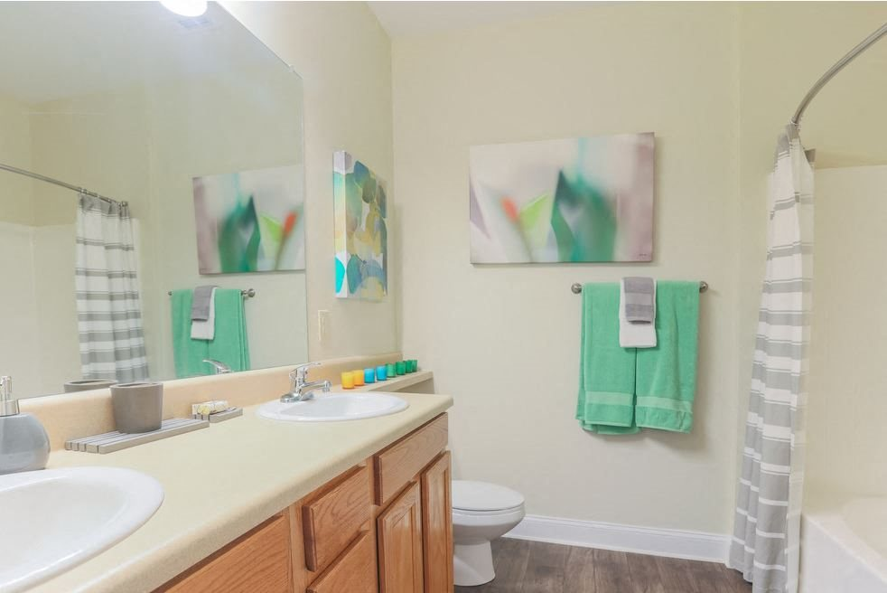 Enjoy a spacious bathroom with oversized garden tubs, curved shower rods and double vanity