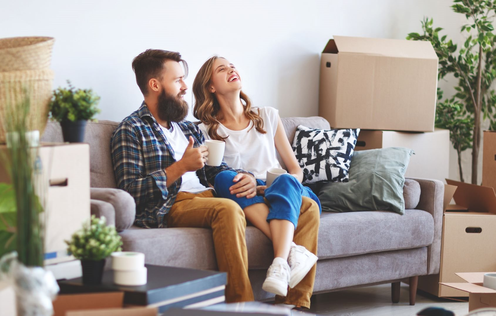 Two people on the couch with moving boxes around them