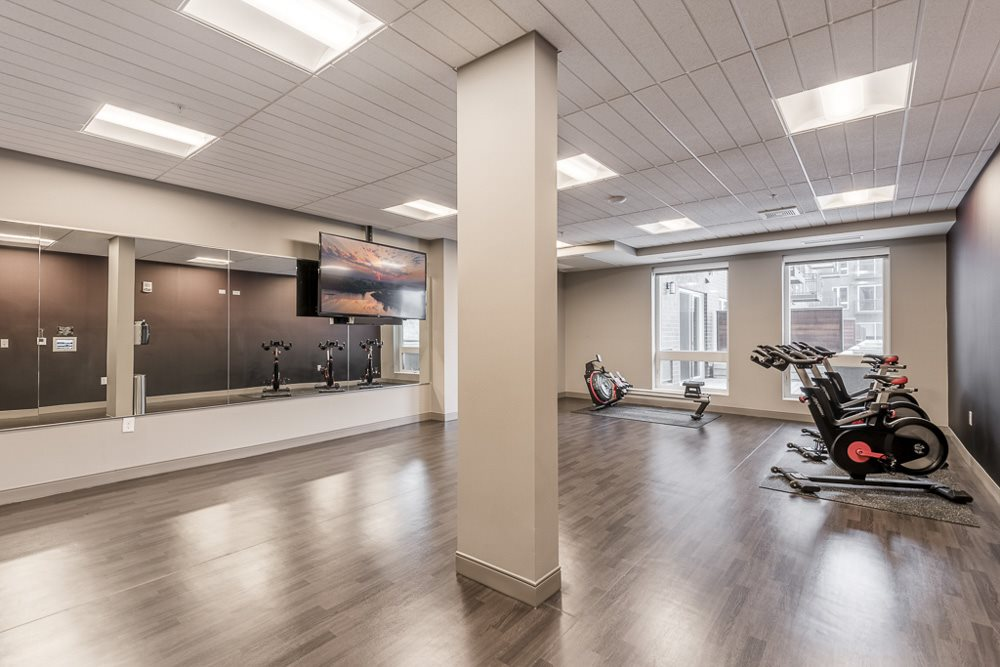 Spin and yoga studio with TV screen for on-demand fitness classes