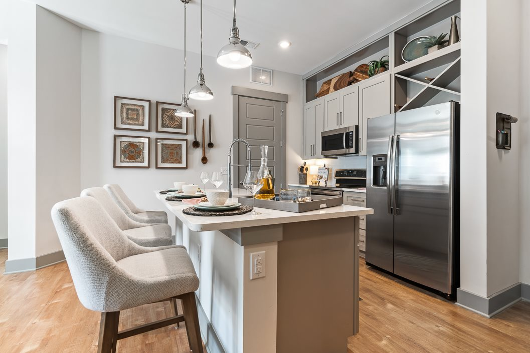 Kitchen island breakfast bar with designer chairs and stainless steel appliances