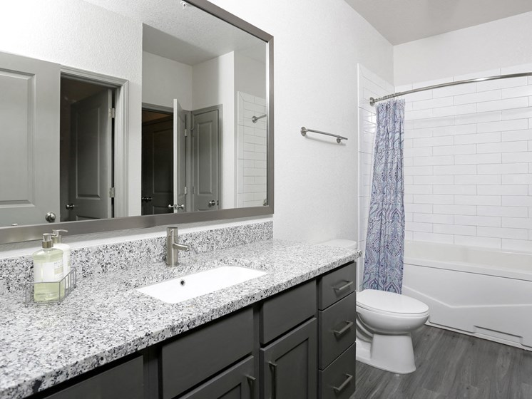 Axis West Bathrooms with Granite Countertops and Subway Tiled Baths