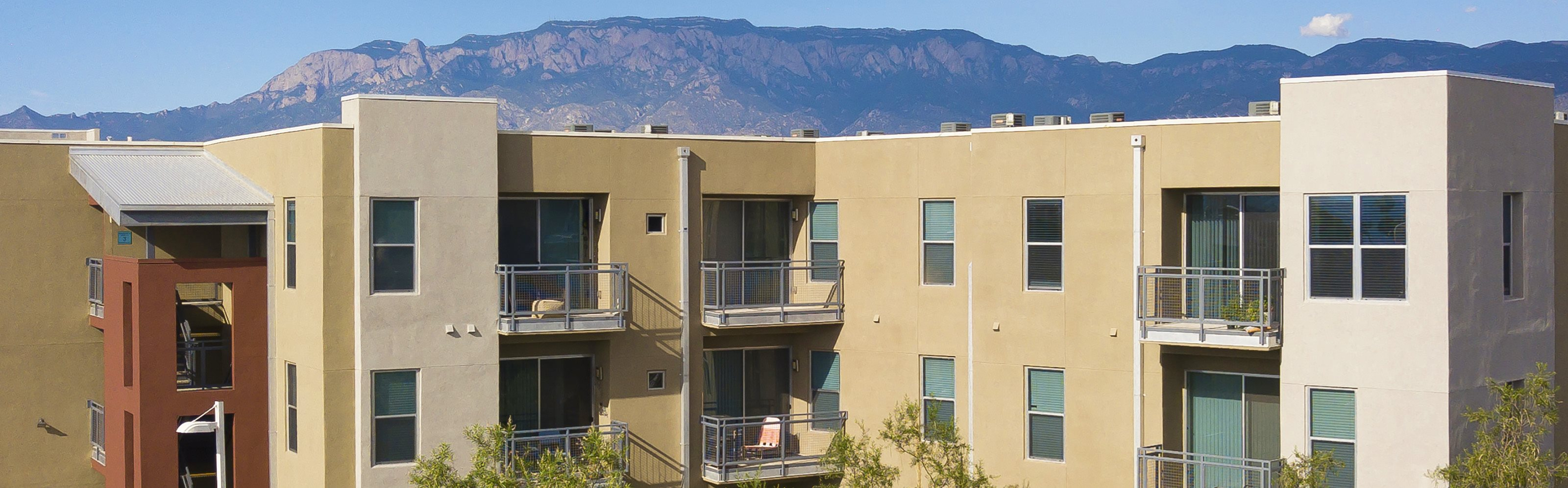 ABQ Uptown Apartments - Exterior building with mountain range background